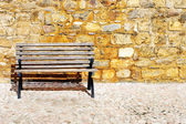 Wood bench against a brick wall — Stock Photo