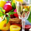 Glass of  white wine and plums — Stock Photo
