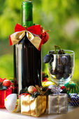 Decorated bottle of red wine with Christmas presents. — Stock Photo