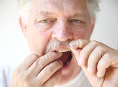 Senior man flosses teeth — Stock Photo