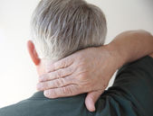Senior man with hand on neck — Stock Photo
