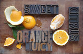 Orange cut and peeled with related words — Stock Photo