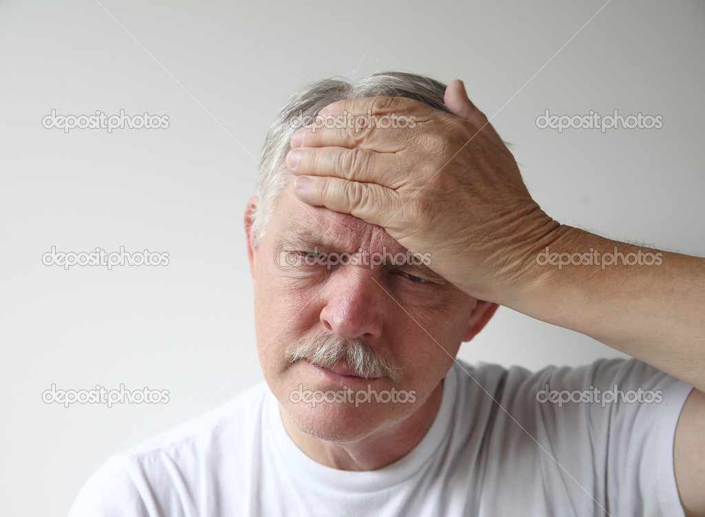 A man puts his hand to his forehead in pain  Stock Photo #12666149