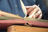 L'homme regarde à travers les livres — Photo