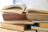 Open book on top of stacks — Stock Photo