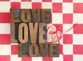 Love words with heart on checked background — Stock Photo