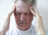 Temple headache in older man — Stock Photo