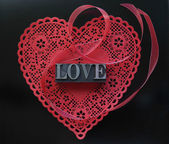 Red heart doily with love on black — Stock Photo