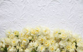 White embossed background with yellow flowers — Stock Photo