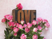 Love word in wood type with roses — Stock Photo