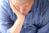 Older man slumped in depression — Stock Photo