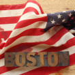 Boston word on a bloodied American flag - Stock Photo