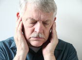 Senior with pain in front of ears — Stock Photo