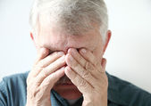 Older man covers eyes with hands — Stock Photo