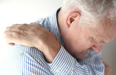 Senior reaches to scratch his back — Stock Photo