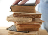 Hand of a man on old books — Stock Photo