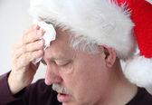 Senior in Santa hat mops his brow — Stock Photo