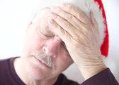 Baş ağrısı ile Santa şapka takan adam — Stok fotoğraf