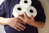 Man with upset stomach holds toilet paper — Stock Photo
