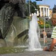Boy splashing water by fountain - Stock Photo