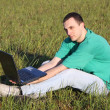Stock Photo: Boy in green t-shirt with laptop