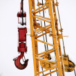 Foto Stock: Yellow crane with red hook