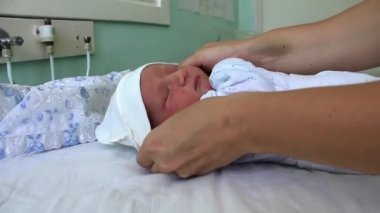 Mother and newborn daughter in maternity hospital