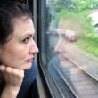 Woman sits in train near window during movement — Stock Video