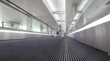 People on travelator inside waiting space in international airport — Stock Video