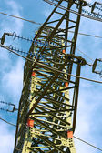 Electricity pylon against blue cloudy sky — Stok fotoğraf
