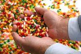Hands full of medication pill capsules — Stock Photo
