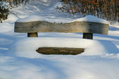 Wooden bench covered with snow — Stok fotoğraf