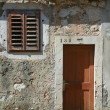 Wooden door and window on stone wall, building facade, Pag, Croatia — Stock Photo
