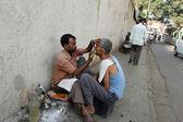 Street barber shaving a man on a street in Kolkata, West Bengal, India — Stock Photo