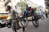 Rickshaw man pulls the customer in the streets of Kolkata, India — Stock Photo