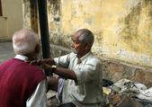 Street barber shaving a man on a street in Kolkata — Stock Photo