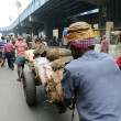 Постер, плакат: Hard working Indians pushing heavy load through streets in Kolkata
