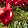 Christmas ball (heart) on the tinsel background — Stock Photo
