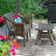 Rattan patio chair and table - Stock Photo