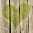 Green heart on old wood — Stock Photo