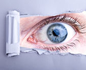 Scary eye looking trough ripped pape — Stock Photo