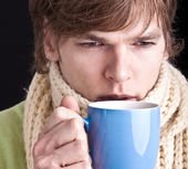 Young man with scarf and hot drin — Stock Photo