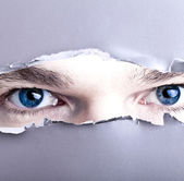 Eyes looking trough ripped pape — Stock Photo