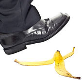 Closeup portrait of a business man foot stepping on banana pee — Stock Photo
