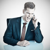 Angry young businessman screaming into his cellphon — Stock Photo