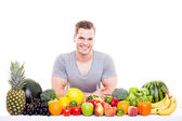 Handsome muscular man sitting behind a row of fruits and vegetab — Stock Photo