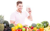Athletic man drinking a protein shake behind a table full of veg — Stock Photo