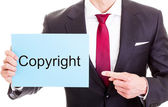Copyright concept - businessman showing card with the word copyr — Stock Photo