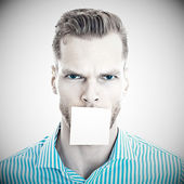 Young man with blank note on his mout — Stock Photo
