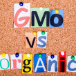 The phrase GMO vs organic in cut out magazine letters pinned to  — Stock Photo #49816675